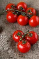 tomates suculentos vermelhos em pano de juta