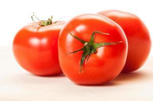 três tomates vermelhos perfeitos em uma placa de madeira foto