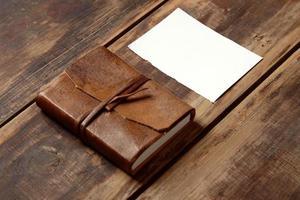 caderno de couro e folha de papel em uma mesa de ooden foto