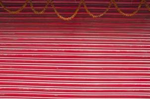 porta de metal ondulada pintada de vermelho e guirlanda de flores