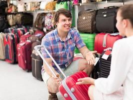 casal escolhendo mala na loja foto