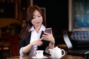 linda garota asiática usando telefone inteligente em um café foto