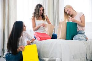 três garotas com muitas sacolas de compras foto