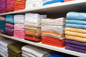 prateleiras com toalhas na loja foto