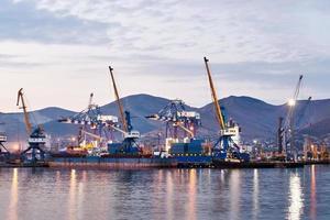 guindastes portuários na doca pelo mar no crepúsculo foto