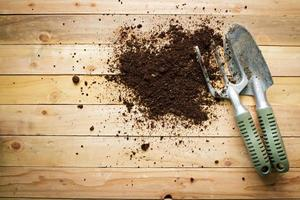 pequena pá de jardinagem e garfo em fundo de madeira. foto