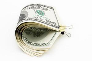 nota de cem dólares com um clipe em um fundo branco foto