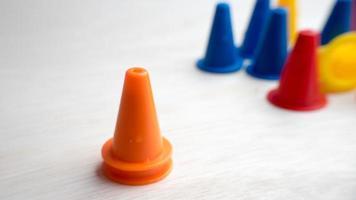 mini cones de segurança plásticos de várias cores na superfície de madeira foto