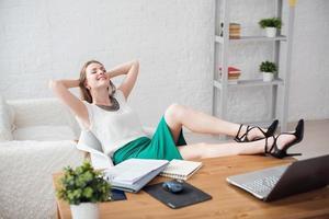 empresária descansando pernas relaxantes sobre as mãos da mesa atrás dela
