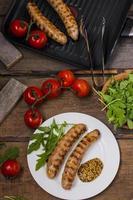 salsichas na grelha com tomate e rúcula foto