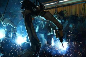 robôs de soldagem de grupo estão trabalhando na indústria de peças automotivas. foto