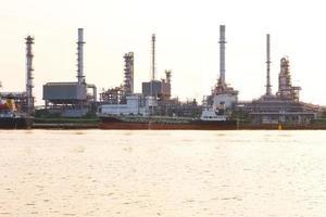 refinaria de petróleo com o navio de carga estacionando perto do rio foto
