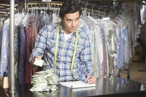 homem calcular recibos enquanto escrevia no bloco de notas na lavanderia