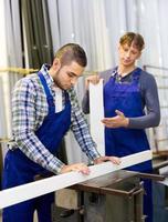 trabalhadores cortando perfis de janelas foto