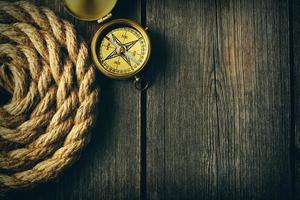 bússola antiga e corda sobre fundo de madeira foto