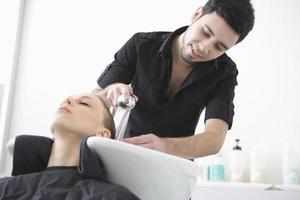 cabeleireiro, lavando o cabelo do cliente no salão foto