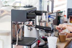 mão fazer uma xícara de café com leite máquina de café. foto