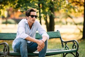 homem atraente, sentado sozinho no banco com celular foto