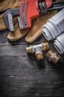 chave de tubulação acessórios de encanamento de cobre luvas de segurança blueprint rol foto