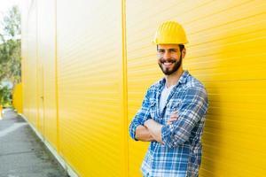 trabalhador adulto com capacete na parede amarela foto