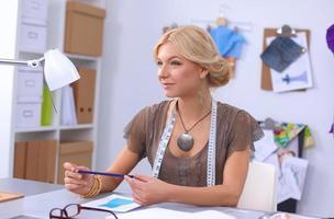 designer de moda jovem moderna trabalhando no estúdio foto