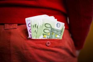 euros no bolso da calça vermelha foto