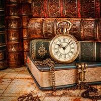 livros antigos e relógio de bolso vintage foto