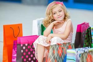 menina com sacolas de compras vai para a loja foto