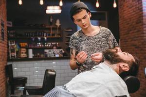 barbeiro barbear homem barbudo com navalha foto