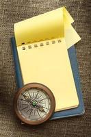 bússola vintage e bloco de notas amarelo em branco foto