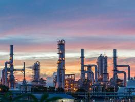 silhueta da refinaria de petróleo e gás no crepúsculo foto