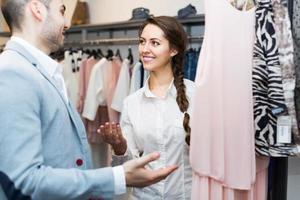 menina de loja, ajudando o cliente na boutique foto