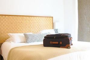mala na cama dentro de um quarto de hotel