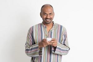 homem indiano casual maduro, usando aplicativos móveis foto