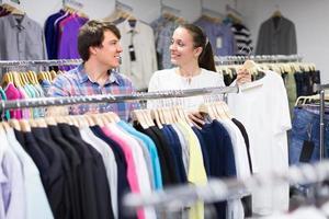 casal fazendo compras na loja de roupas foto