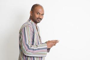 homem indiano casual maduro jogando jogos de smartphone foto
