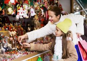 mãe com filha pequena olhando para o balcão de marke de natal foto