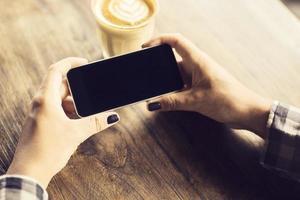 mãos de menina com smartphone e café em uma mesa de madeira foto