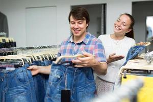 casal escolhendo jeans azul na loja foto