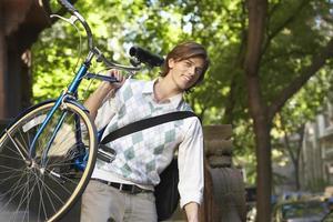 empresário carregando bicicleta ao ar livre