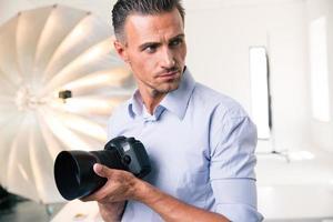 fotógrafo, segurando a câmera e olhando para longe
