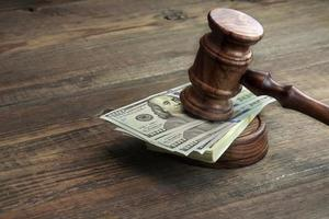 juízes martelo, tampo e maço de dinheiro em cima da mesa foto