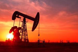 uma silhueta de uma bomba de óleo em um campo de petróleo ao pôr do sol foto