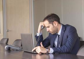 empresário preocupado, segurando sua cabeça foto