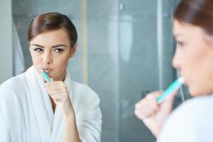 jovem mulher bonita, escovar os dentes foto