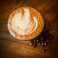 latte art e grãos de café na madeira foto