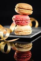 pilha de biscoito francês colorido na ardósia com fundo preto foto
