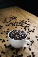 xícara cheia de grãos de café foto
