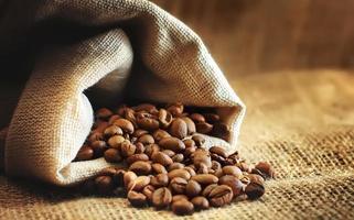 grãos de café torrados saem do saco foto