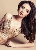 linda garota com cabelos escuros na luxuosa lantejoulas vestido foto